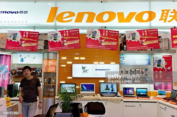 A Chinese vendor smiles under a Lenovo sign at a computer center in Shanghai on August 19 2010 Lenovo Group China's biggest personal computer maker...