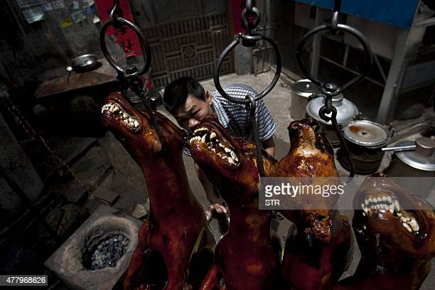 A Chinese vendor waits for customers as he hangs up cooked dogs at his stall in Yulin in southern China's Guangxi province on June 21 2015 The city...