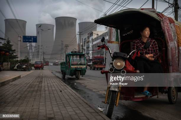 Chinese vendor waits for customers as she sells vegetables at a local market outside a state owned coal fired power plant near the site of a large...