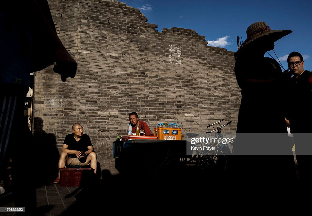 Chinese vendors sell cold drinks in front of t he wall of an old destroyed Hutong or traditional house on June 12 2015 in Beijing China Many of the...