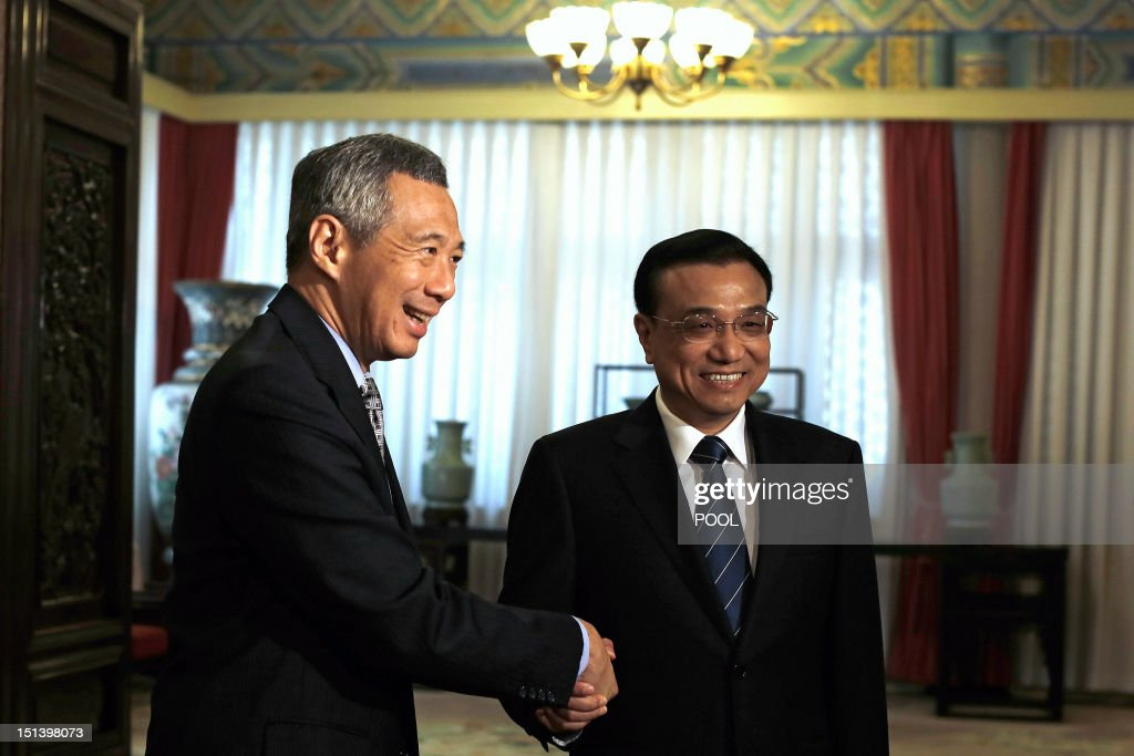 Chinese Vice Premier Li Keqiang (R) shakes hands with Singapore Prime Minister Lee Hsien Loong (L) at the Ziguangge Pavilion in the Zhongnanhai leaders' compound in Beijing on September 7, 2012. Lee is on an official six-day visit to China. AFP PHOTO / POOL / Lintao Zhang