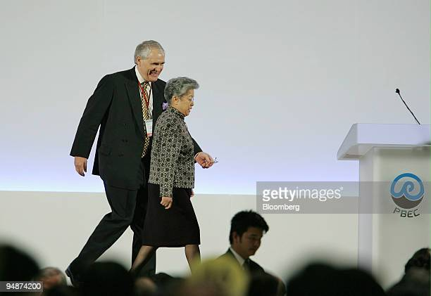 Chinese Vice Premier Wu Yi center right is escorted to the podium by Pacific Basin Economic Council Chairman David Eldon before she spoke to...