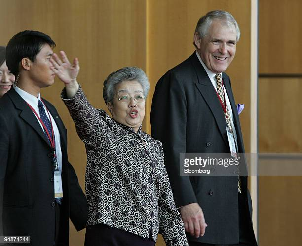 Chinese Vice Premier Wu Yi waves as she is escorted from a conference hall by Pacific Basin Economic Council Chairman David Eldon right and a...