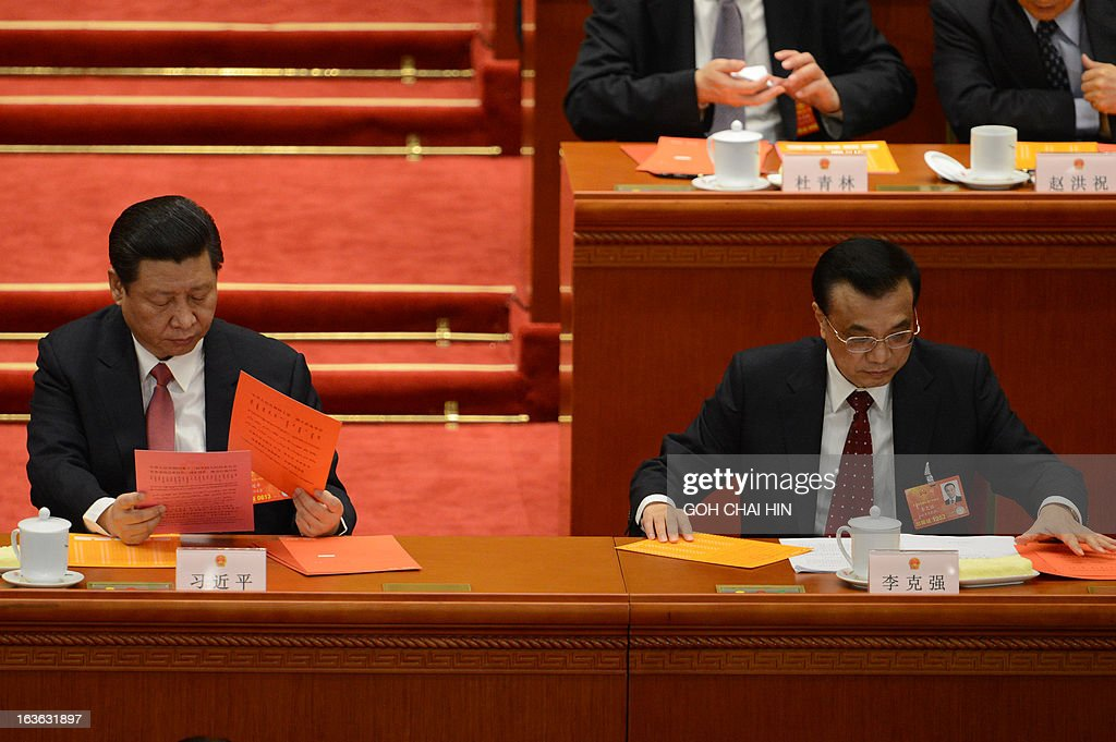 Chinese Vice President Xi Jinping (L) and Vice Premier Li Keqiang read the ballot papers prior to the election for the new president of China during the 12th National People's Congress (NPC) in the Great Hall of the People in Beijing on March 14, 2013. China's parliament is to name Xi Jinping as the country's new president on March 14, formalising his leadership of the world's most populous nation four months after he took charge of the ruling Communist Party.