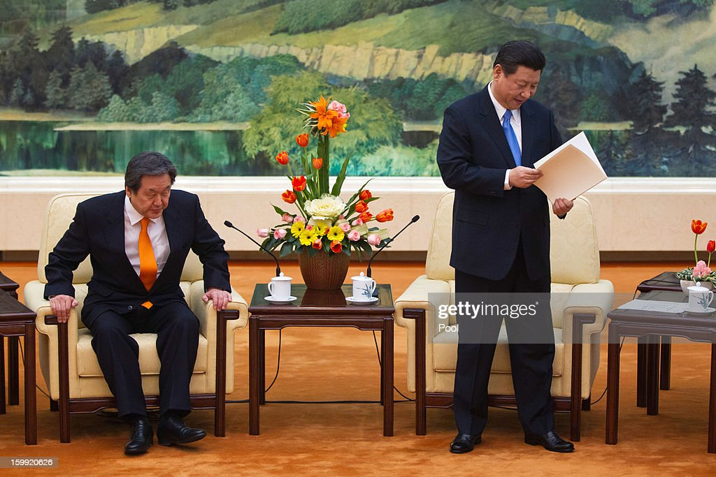 Chinese Vice President Xi Jinping, (C) checks a letter from South Korean President-elect Park Geun-hye, while Kim Moo-sung, (L) special envoy sent by Park, takes his seat after delivering the letter during their meeting at the Great Hall of the People on January 23, 2013 in Beijing, China.
