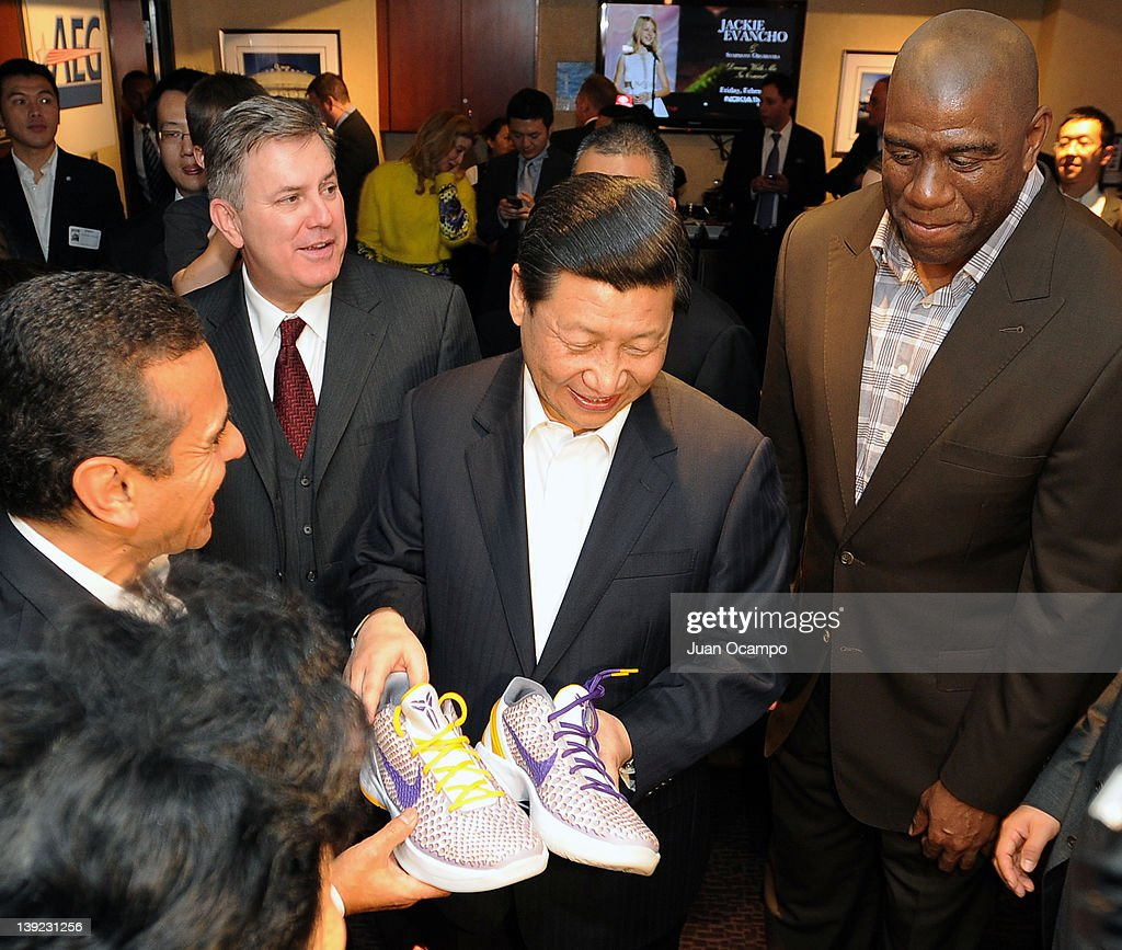 Chinese Vice President Xi Jinping is presented with a pair of shoes by Los Angeles Mayor Antonio Villaraigosa AEG President and CEO Tim Leiweke and...