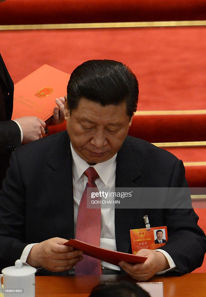 Chinese Vice President Xi Jinping read the ballot papers prior to the election for the new president of China during the 12th National People's Congress (NPC) in the Great Hall of the People in Beijing on March 14, 2013. China's parliament is to name Xi Jinping as the country's new president on March 14, formalising his leadership of the world's most populous nation four months after he took charge of the ruling Communist Party. AFP PHOTO /GOH CHAI HIN