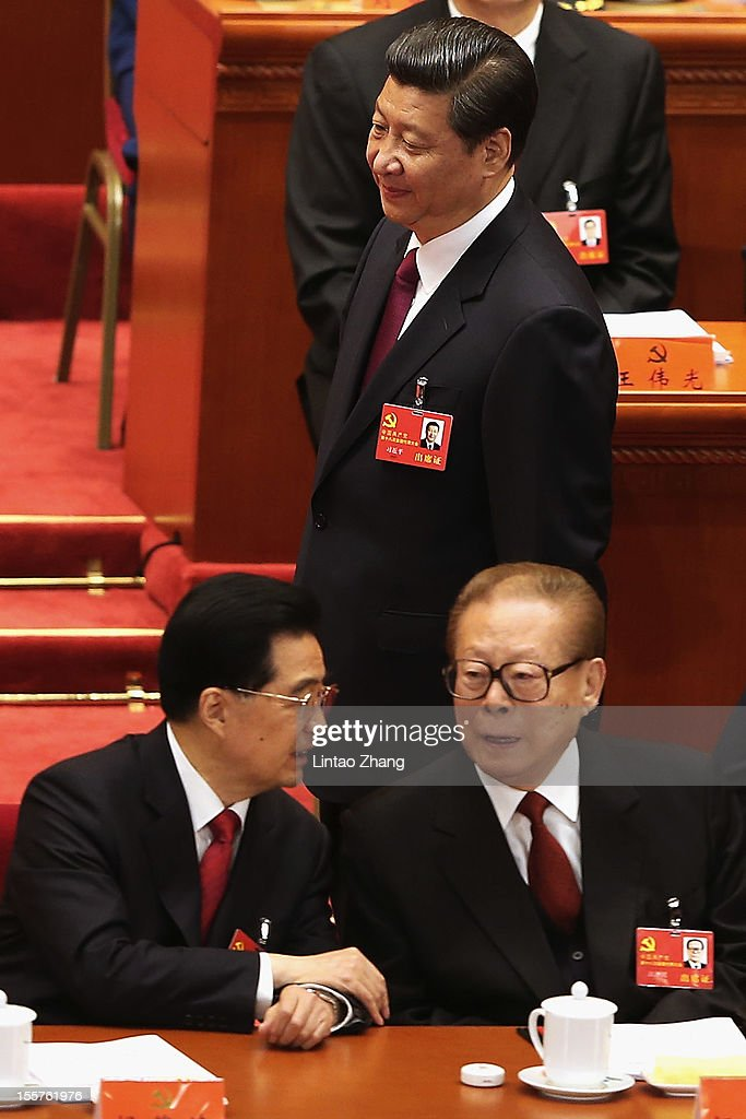 Chinese Vice President Xi Jinping walk past Chinese President Hu Jintao and former Chinese President Jiang Zemin during the opening session of the...
