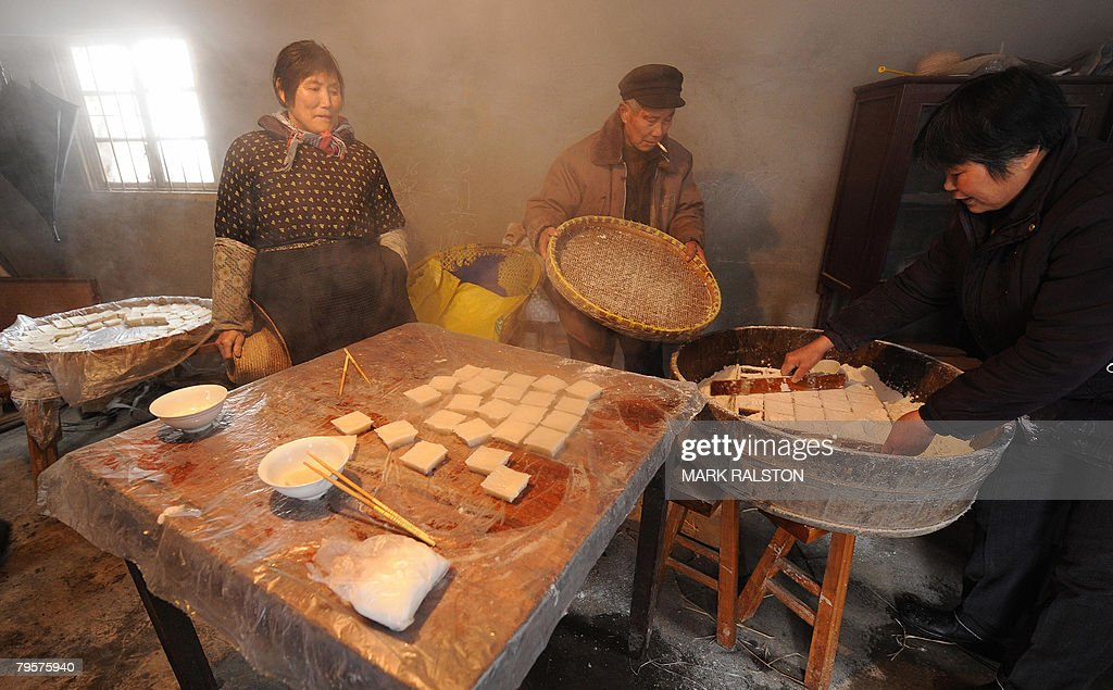 Chinese villagers prepare traditional new year rice cakes called nian gao at the village of Zhangjia in Jiangsu Province on February 1 2008 The...