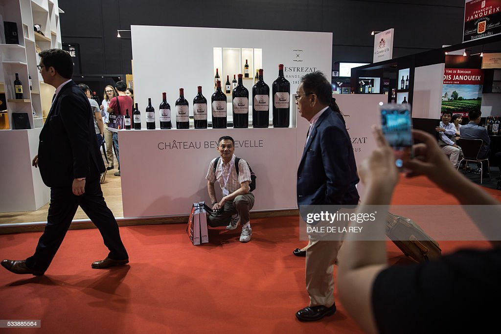 A Chinese visitor (C) poses for a photograph in front of a booth at Vinexpo in Hong Kong on May 24, 2016. The international wine and spirits exhibition runs from May 24 to 26. / AFP / DALE