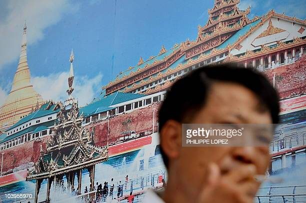 A Chinese visitor smokes a cigarette in front of a billboard displayed on a wall of the Myanmar pavilion at the World Expo 2010 in Shanghai on...