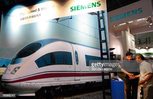 Chinese visitors look at a Siemens booth at an exhibition in Beijing 07 September 2007 Chinese justice officials are probing a possible case of...