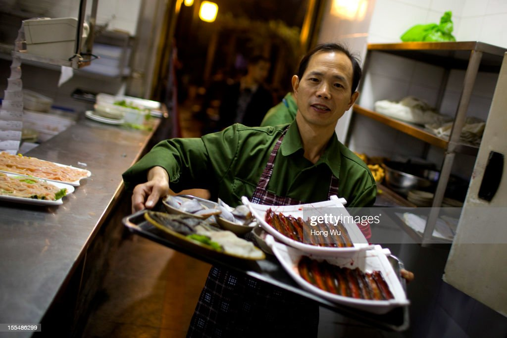 A Chinese waiter, wearing an old military uniform, works in the kitchen of a chafing dish restaurant on November 4, 2012 in Chongqing, China. This theme restaurant, which was built in 2005, displays special Chinese red revolution culture of the 1970s that attracts customers with their old style decoration style and red revolution atmosphere.