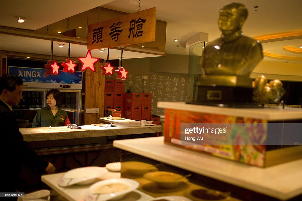 A Chinese waitress, weaing an old military uniform, stands next to a statue of Mao Tse-tung, at a chafing dish restaurant on November 4, 2012 in Chongqing, China. This theme restaurant, which was built in 2005, displays special Chinese red revolution culture of the 1970s that attracts customers with their old style decoration style and red revolution atmosphere.