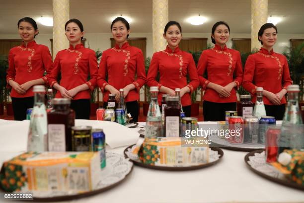 Chinese waitresses wait ahead a welcome banquet for the Belt and Road Forum at the Great Hall of the People in Beijing on May 14 2017 China touted...