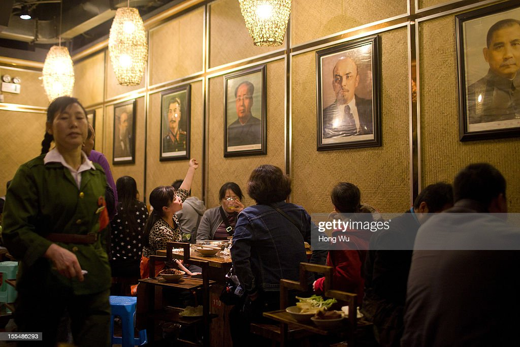 Chinese waitresses wearing old military uniform, serve guests under portraits of Marx, Engels, Stalin and Mao Tse-tung at a chafing dish restaurant on November 4, 2012 in Chongqing, China. This theme restaurant, which was built in 2005, displays special Chinese red revolution culture of the 1970s that attracts customers with their old style decoration style and red revolution atmosphere.