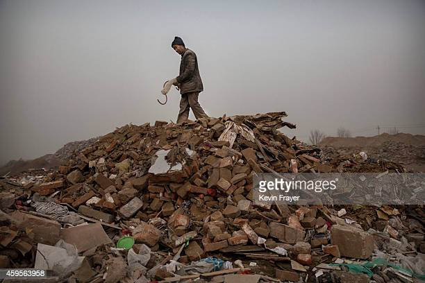 Chinese waste picker stands on a pile of rubble and waste as he looks for items to be scavenged and sold for recycling at a landfill site on November...
