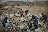 Chinese waste pickers scavenge for items to sell for recycling at a landfill site on November 25 2014 in Beijing China