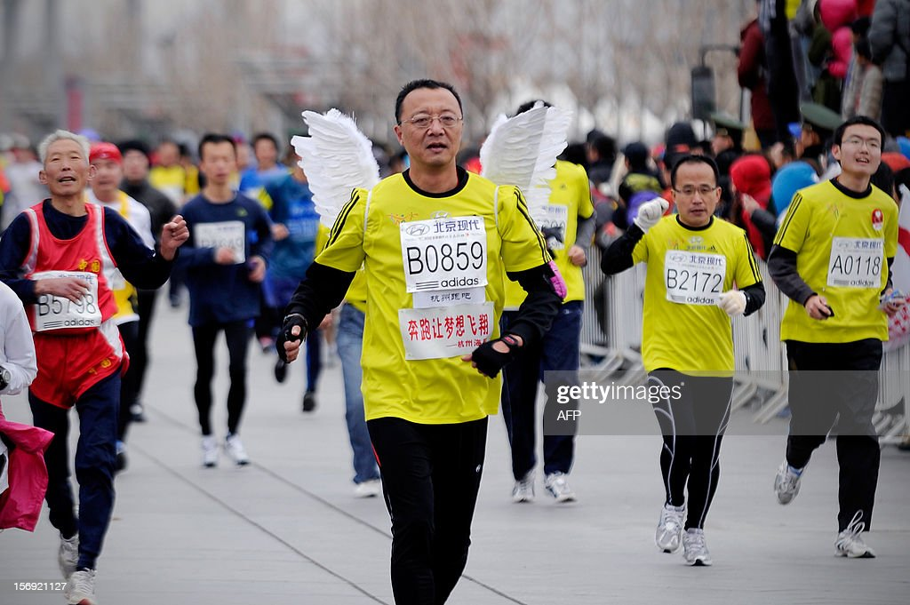 A Chinese wearing a pair of wings takes part in the Beijing Marathon in the Chinese capital on November 25, 2012. A total of 30,000 runners took part in the race. AFP PHOTO / WANG ZHAO