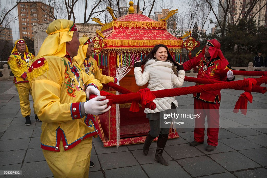 A Chinese woman adjusts her hair before having her picture taken with men dressed in traditional costume at a local fair during Spring Festival celebrations on February 10, 2016 in Beijing, China. The Chinese Lunar New Year also known as the Spring Festival, which is based on the Lunisolar Chinese calendar, is celebrated from the first day of the first month of the lunar year and ends with Lantern Festival on the fifteenth day. This new year marks the Year of the Monkey.