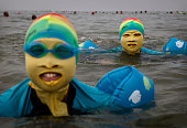 Chinese woman and her daughter wear facekinis while swimming on August 22 2014 in the Yellow Sea in Qingdao China The locally designed mask is worn...