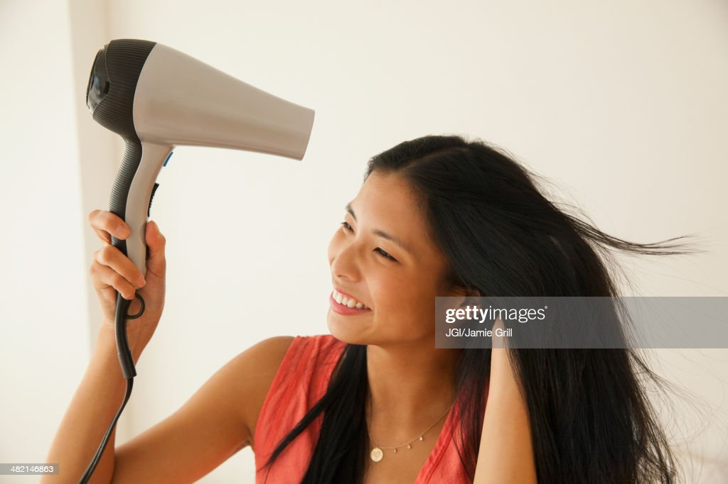 Chinese woman blow drying her hair