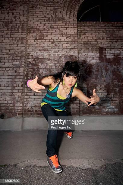 Chinese woman breakdancing in urban area