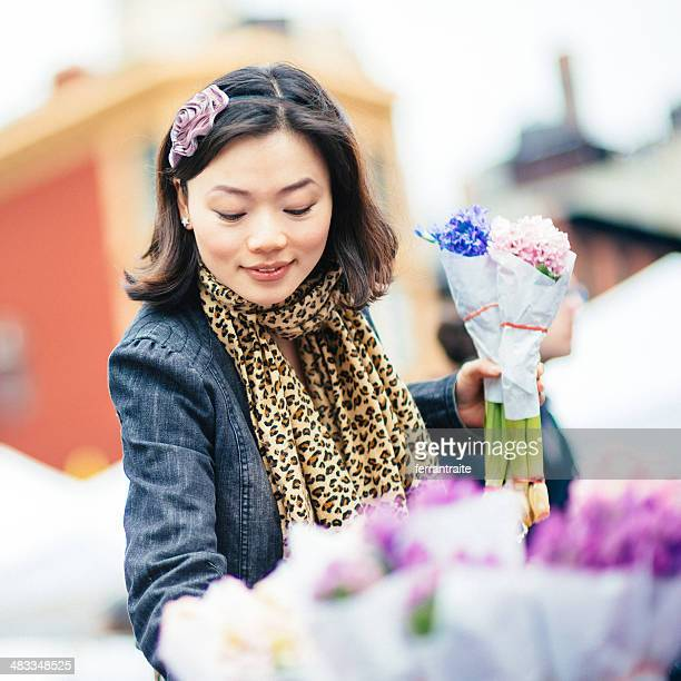 Chinese Woman buys flowers from Street Market Stall