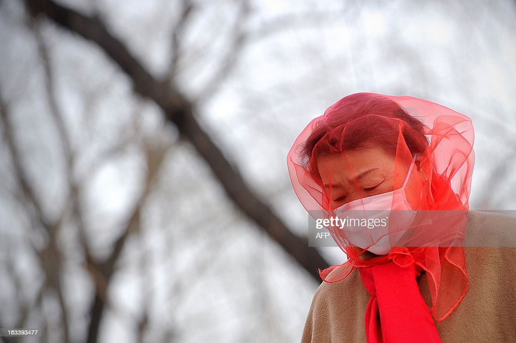 A Chinese woman covers her head with a scarf as she makes walks near Tiananmen Square in Beijing on March 9, 2013. Strong winds and dust storms swept the Chinese capital on March 9.