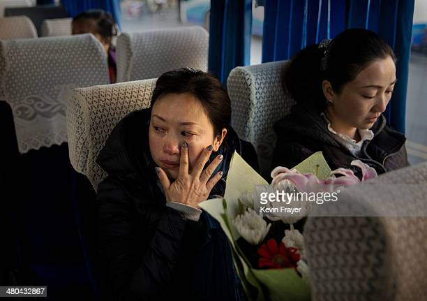 Chinese woman cries as she waits in a bus to be taken to a sea burial ceremony organized by the Funeral and Internment Administration of Shanghai...