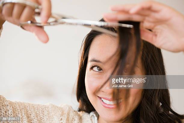 Chinese woman cutting her bangs