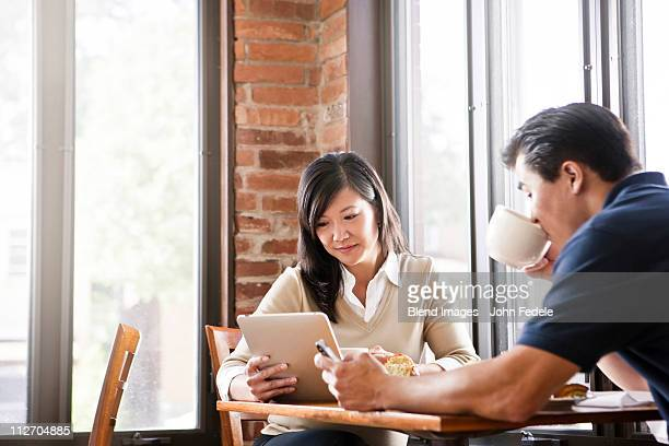 Chinese woman digital tablet to husband in cafe