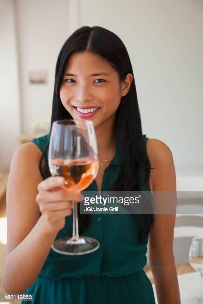 Chinese woman drinking glass of rose wine
