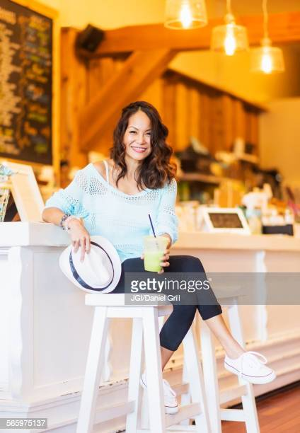 Chinese woman drinking smoothie in cafe