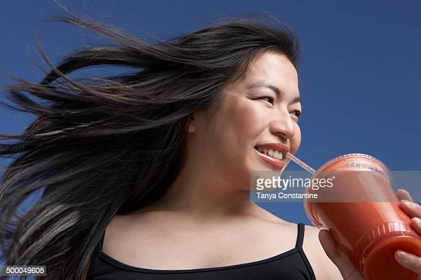 Chinese woman drinking smoothie outdoors