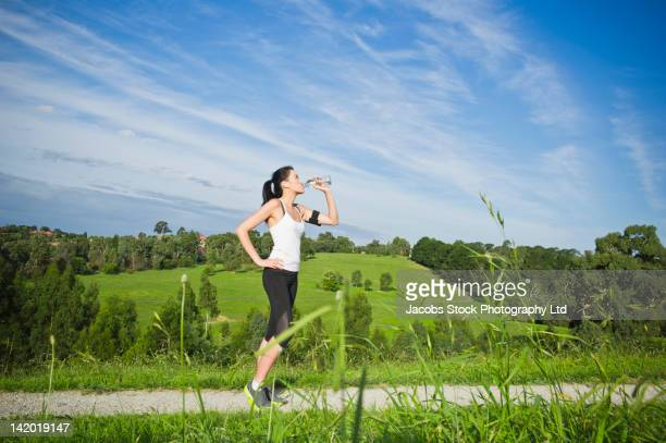 Chinese woman drinking water after exercise
