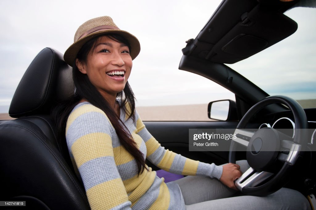 Chinese woman driving convertible : Stock Photo