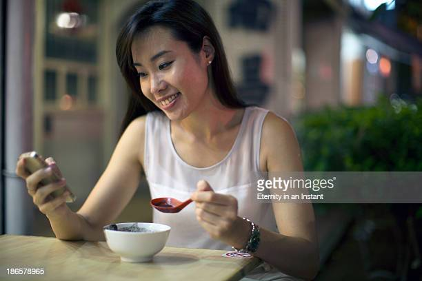 Chinese woman eating and looking at smartphone