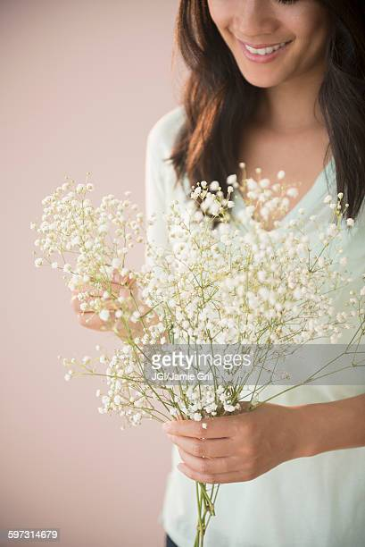 Chinese woman holding bunch of flowers