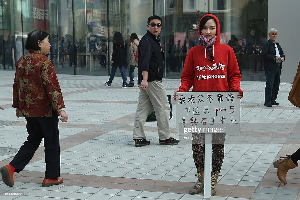 A Chinese woman holds a sign which reads 'My husband is not reliable, he doesn't buy me an iPhone 5, I'm looking for a rich man' outside a newly opened Apple Store in Wangfujing shopping district on October 20, 2012 in Beijing, China. Apple Inc. opened its sixth retail store on the Chinese mainland Saturday. The new Wangfujing store is Apple's largest retail store in Asia.