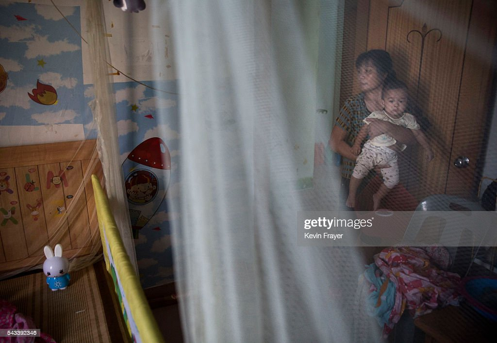 Chinese woman holds her grandson next to a mosquito net in their house on Shazai Island where the Sun YatSen UniversityMichigan University Joint...