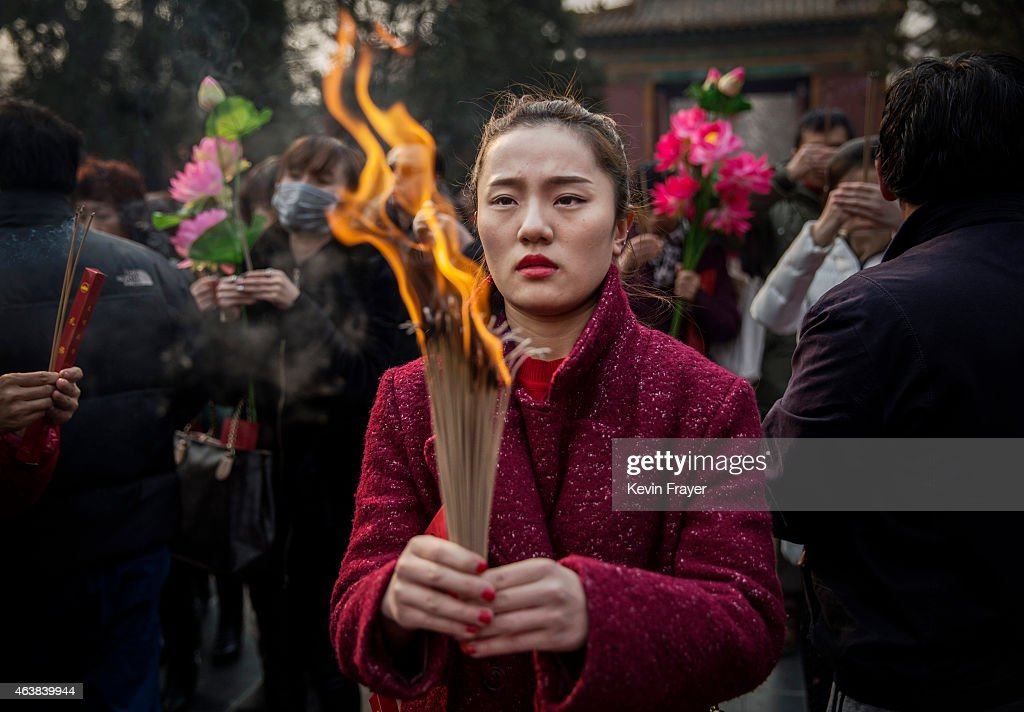 Chinese woman holds incense while praying with others at the Yonghegong Lama Temple during celebrations for the Lunar New Year February 19 2015 in...