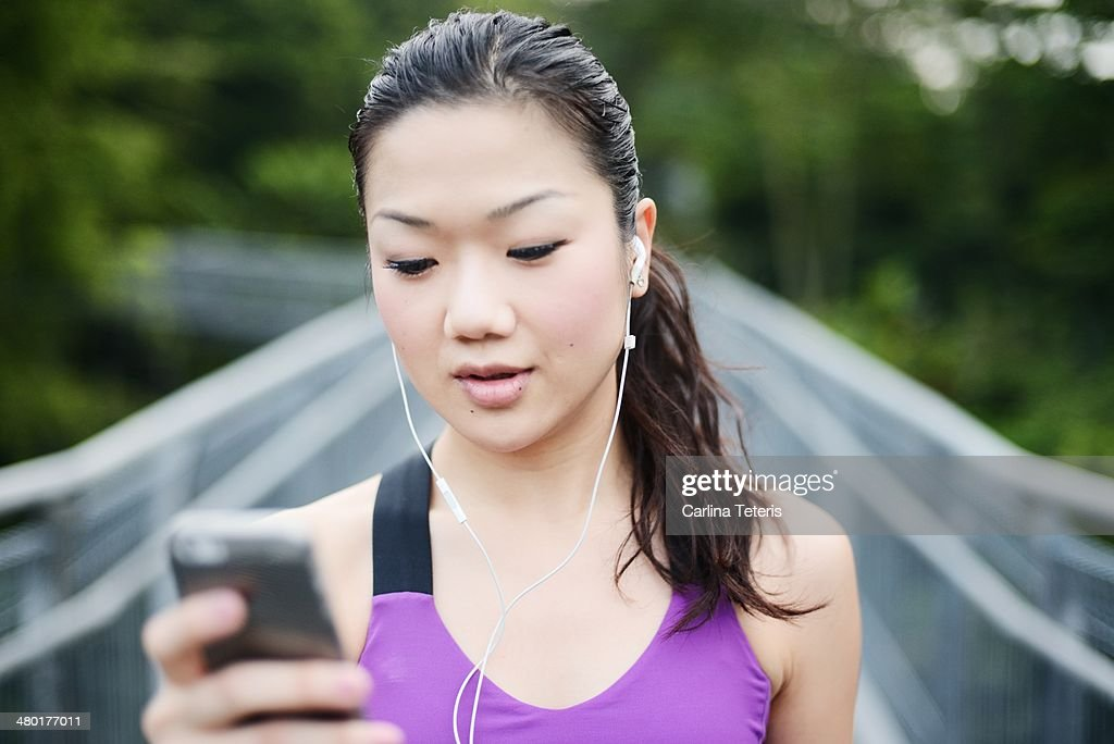 Chinese woman in workout clothes checking phone : Stock Photo