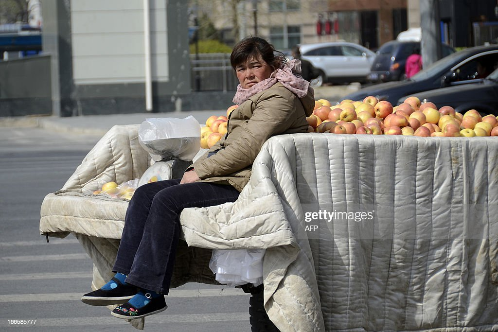 A Chinese woman looks on as she sits on a trailer with apples in Beijing on April 14, 2013. China's economic growth likely picked up slightly in the first quarter of this year, according to an AFP poll of analysts, but they say the rebound is fragile and key data unreliable.