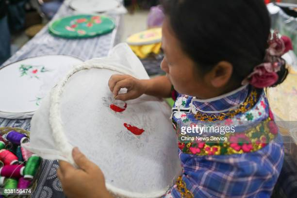 Chinese woman of Bouyei ethnic group makes embroidery at Wangmo County on August 24 2017 in Qianxinan Bouyei and Miao Autonomous Prefecture Guizhou...