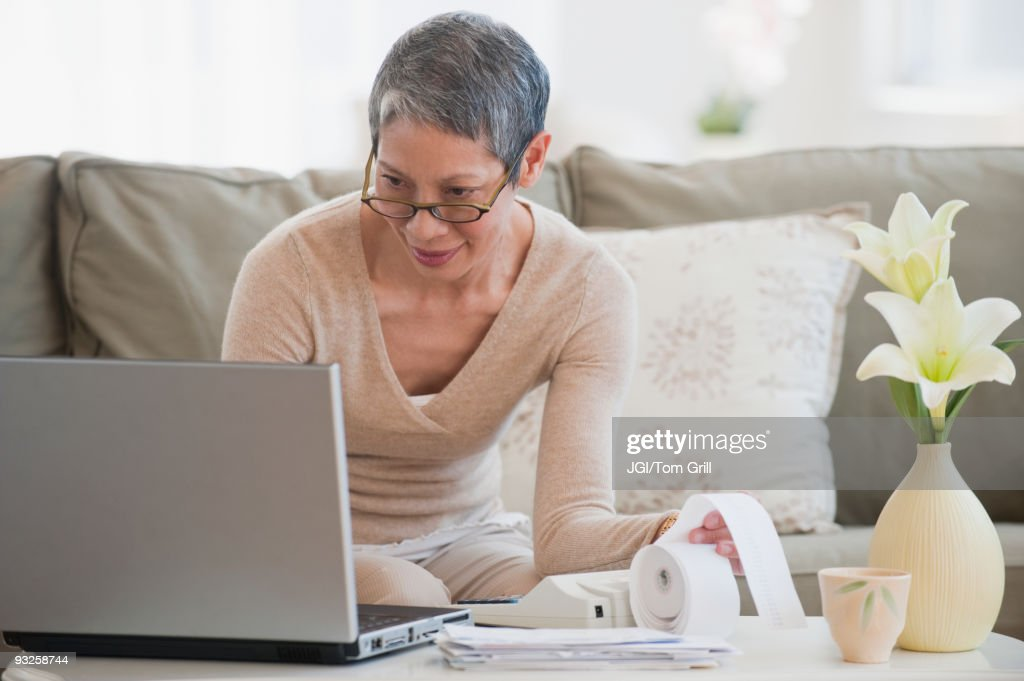 Chinese woman paying bills with laptop in living room : Stock Photo