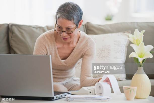 Chinese woman paying bills with laptop in living room