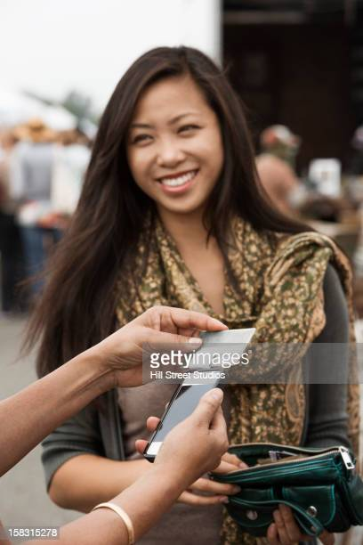 Chinese woman paying with credit card at flea market