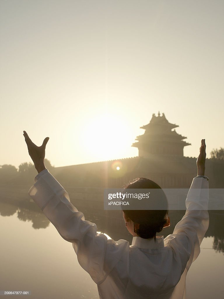 Chinese woman performing tai chi exercises by lake at Forbidden City : Stock Photo