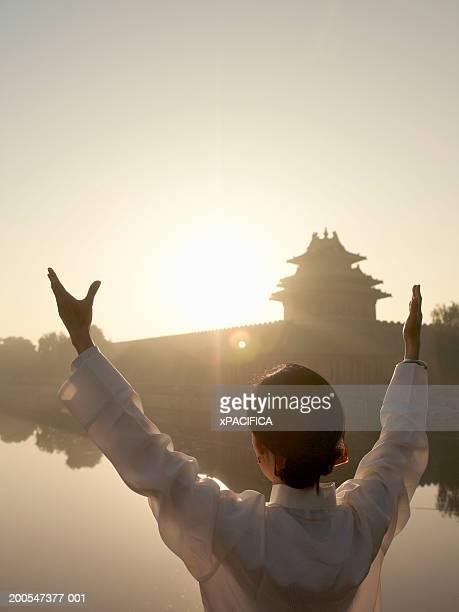 Chinese woman performing tai chi exercises by lake at Forbidden City